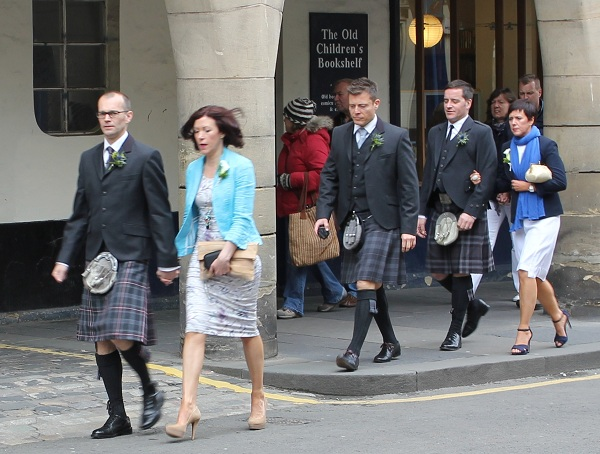 A wedding party dresses in kilts on the Royal Mile in Edinburgh, Scotland